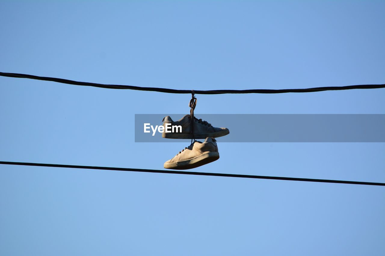 Low Angle View Of Shoes Hanging On Cable Against Clear Blue Sky
