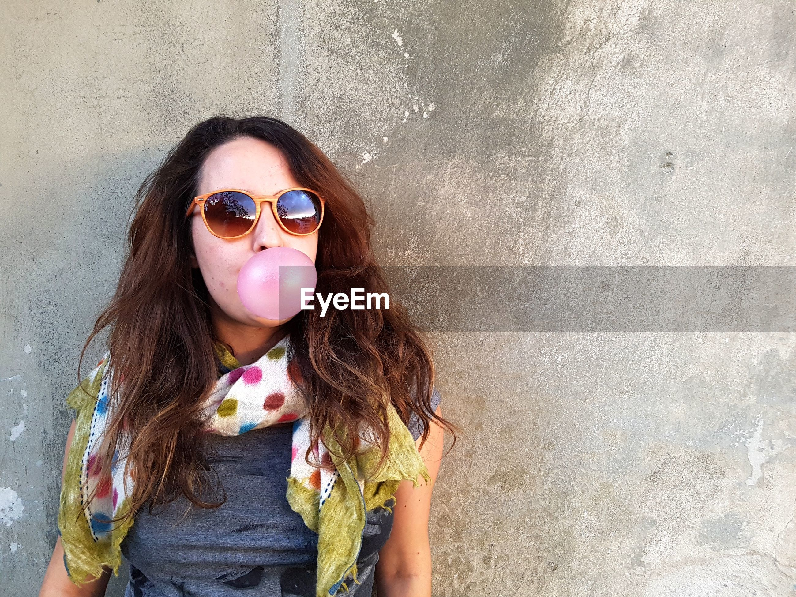 Portrait of woman in sunglasses blowing bubble gum against wall