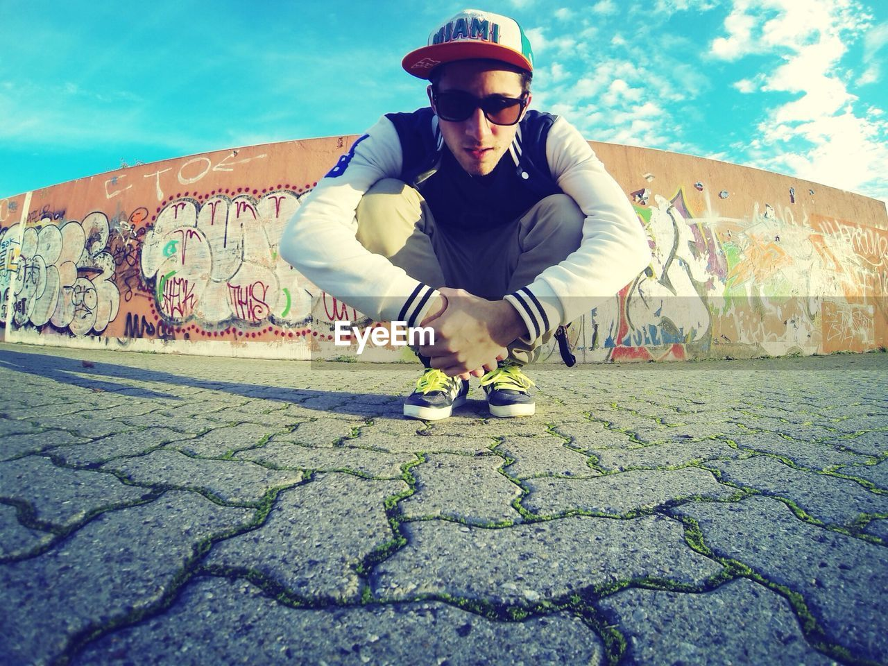 Portrait of young man crouching against graffiti wall