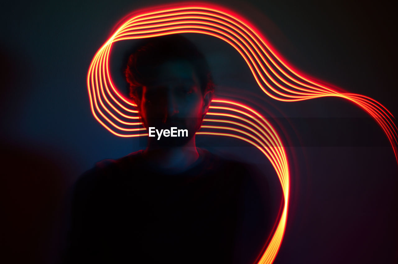 Young man with illuminated light trail against wall