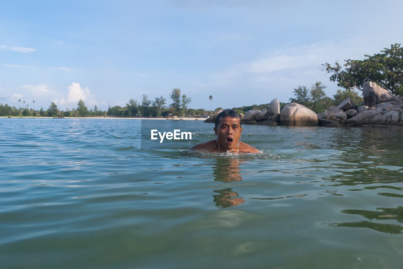 water, waterfront, one person, portrait, lifestyles, leisure activity, real people, headshot, sky, swimming, day, nature, beauty in nature, shirtless, trip, cloud - sky, front view, outdoors, swimming pool