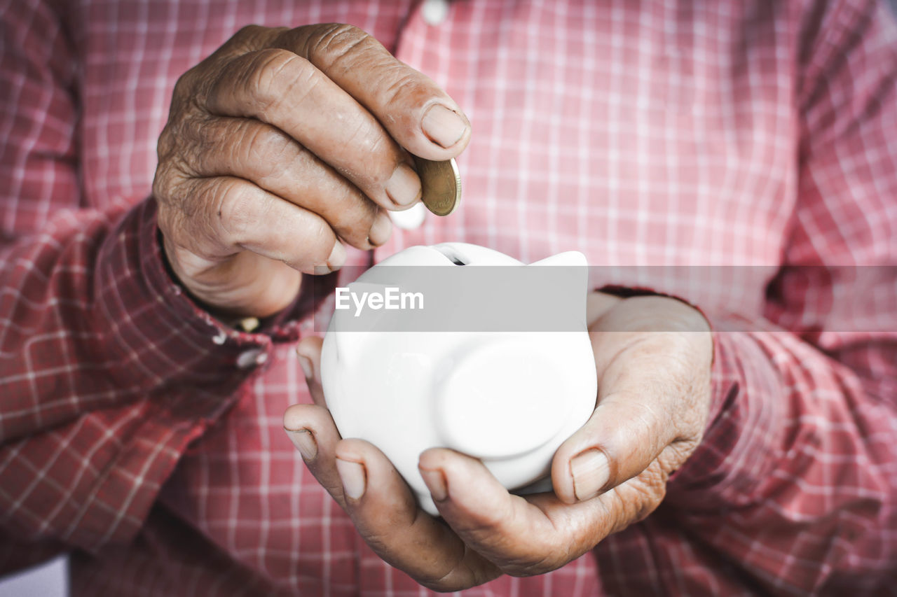 Midsection Of Man Putting Coin In Piggy Bank