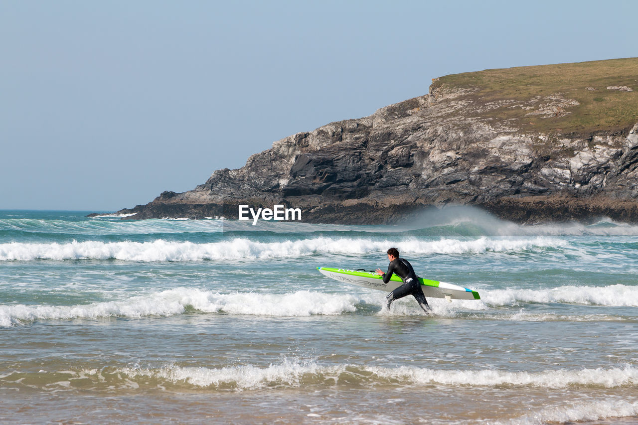sea, water, sky, sport, motion, wave, aquatic sport, leisure activity, beauty in nature, surfing, clear sky, one person, nature, lifestyles, horizon over water, real people, scenics - nature, land, men, outdoors