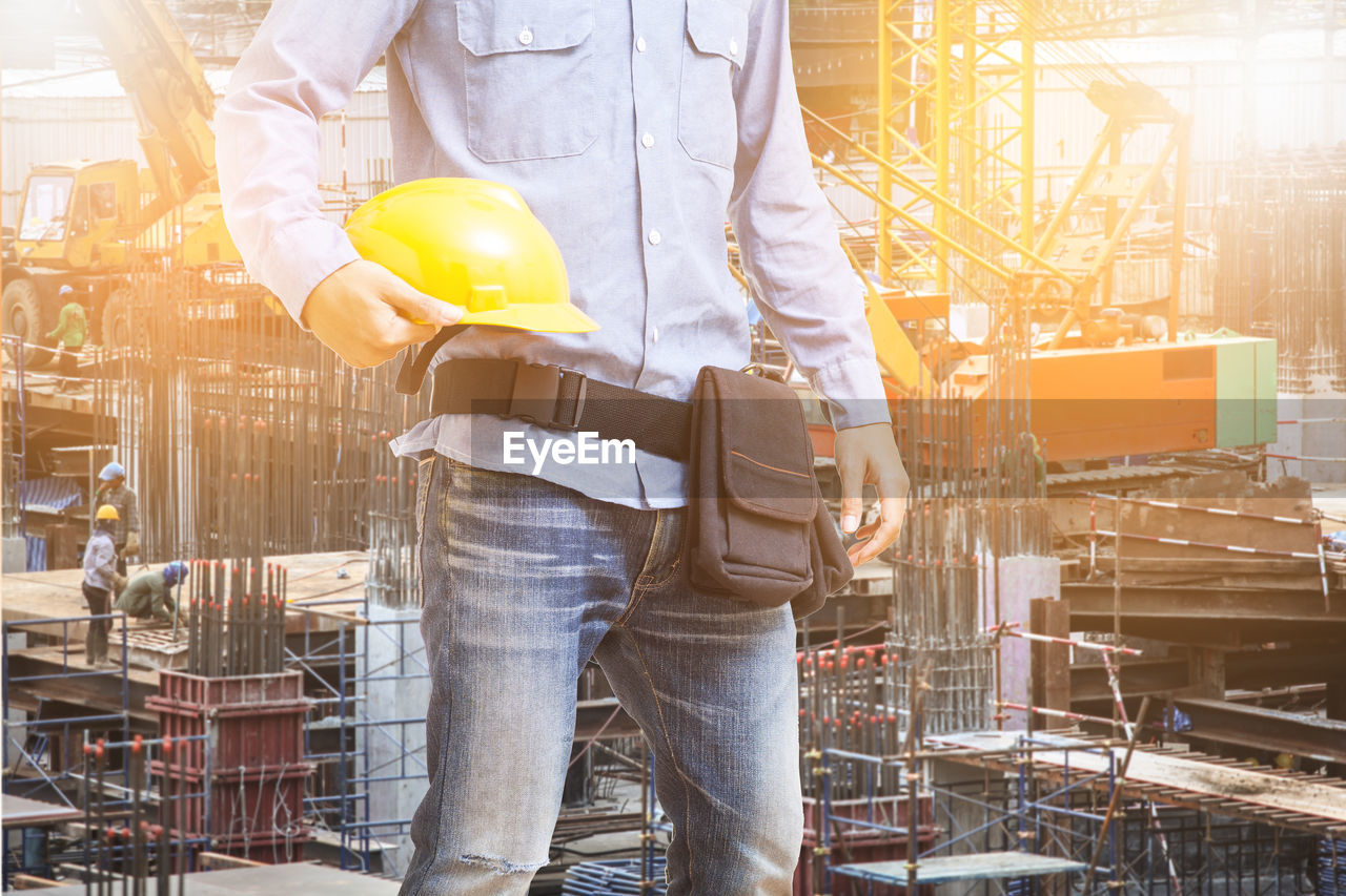 occupation, working, industry, standing, one person, men, midsection, adult, holding, business, construction industry, indoors, protection, protective workwear, construction site, machinery, factory, helmet