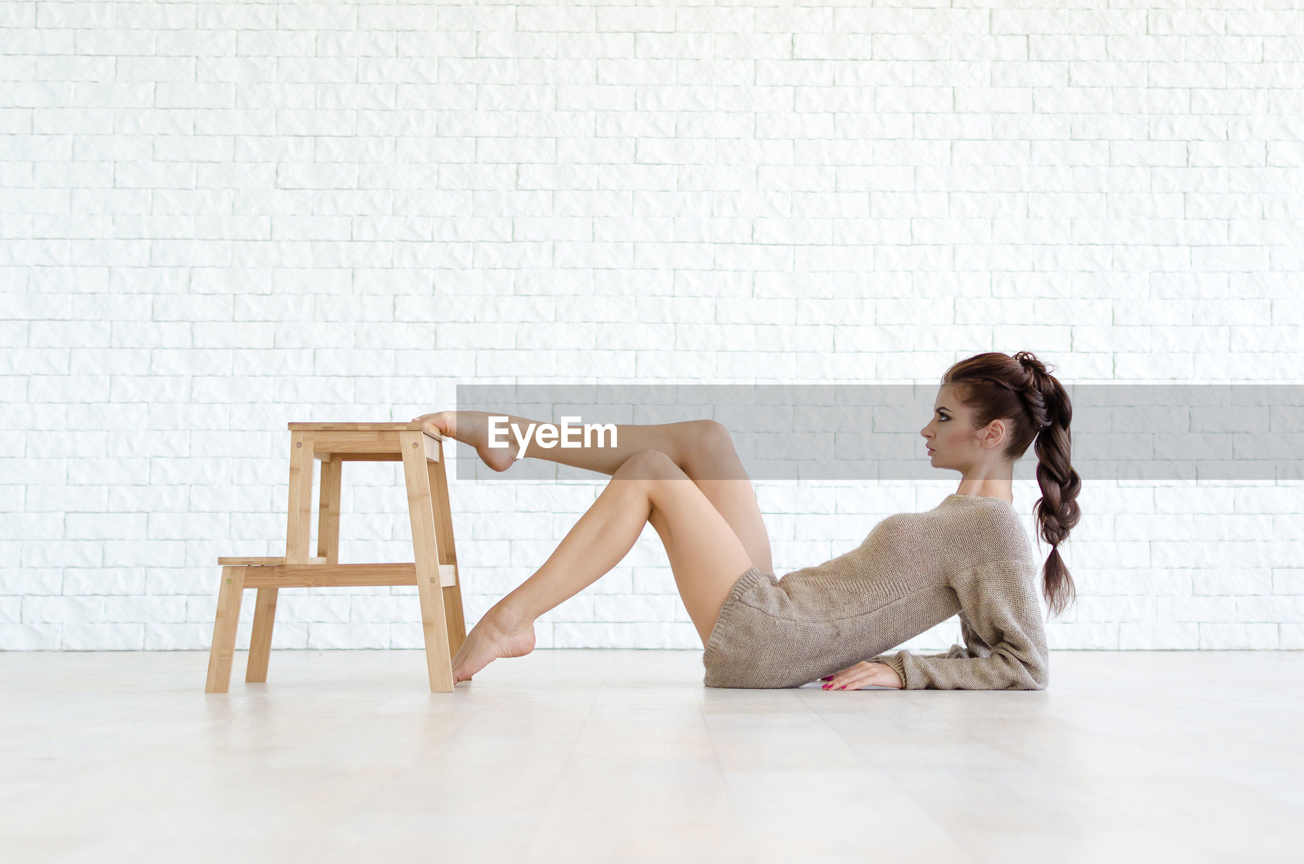 Full length of young woman leaning while pushing stool against brick wall
