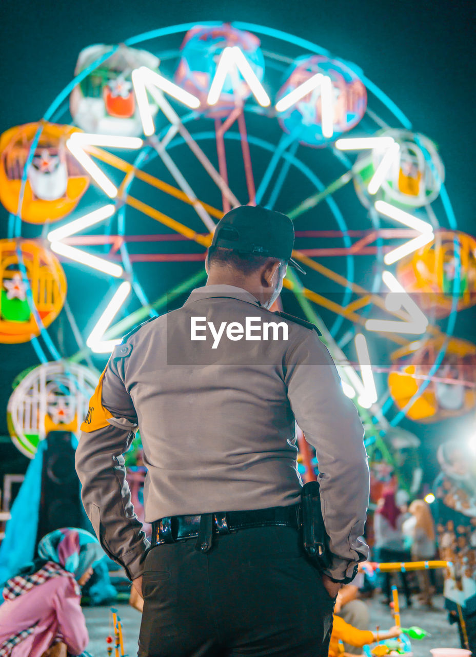 Rear View Of Man Standing Against Illuminated Ferris Wheel At Night