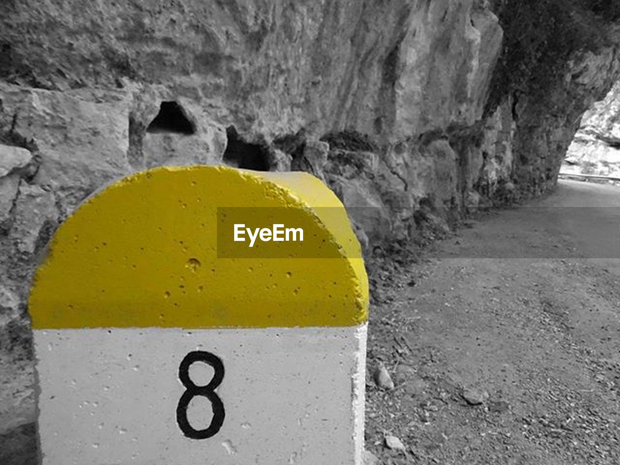 yellow, close-up, street, road, textured, day, no people, asphalt, outdoors, road marking, the way forward, transportation, guidance, rock - object, text, direction, nature, communication, wall - building feature, arch