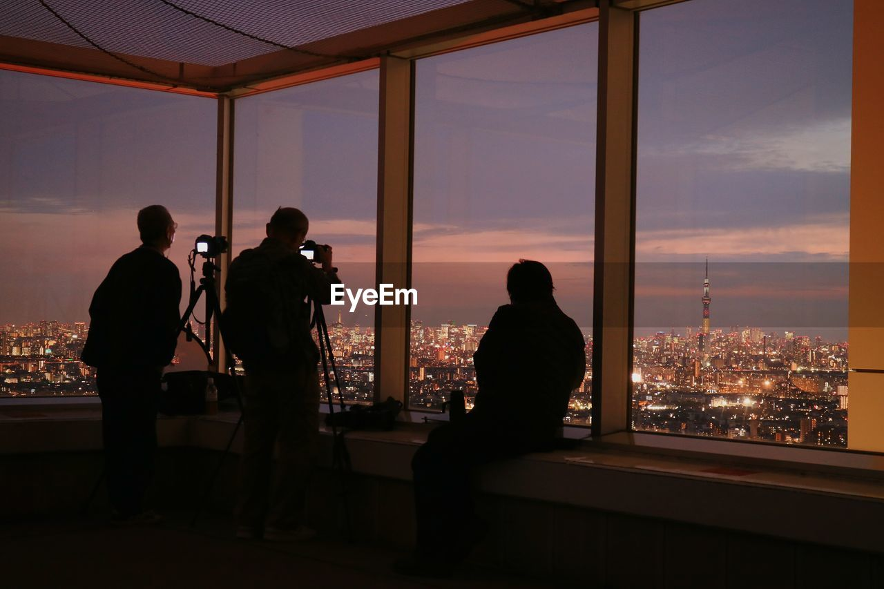 Silhouette Men Photographing Tokyo Sky Tree In City During Sunset