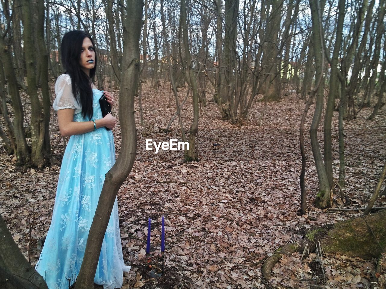 WOMAN STANDING BY BARE TREE IN FOREST