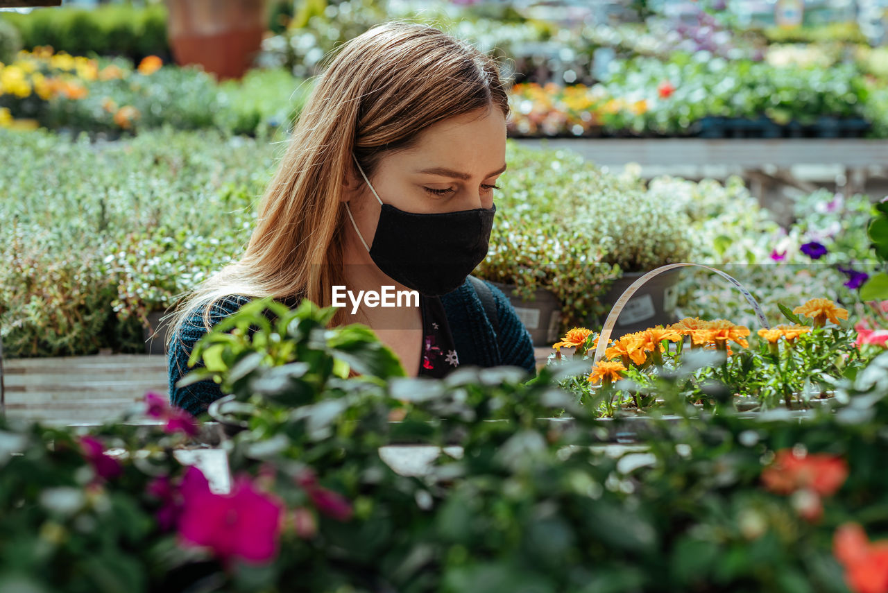 Woman with face mask in greenhouse buying flowers