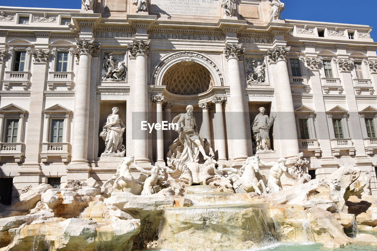 statue, sculpture, human representation, art and craft, architecture, male likeness, building exterior, fountain, built structure, craft, architectural column, travel destinations, history, outdoors, travel, low angle view, day, no people, baroque style, water, sky