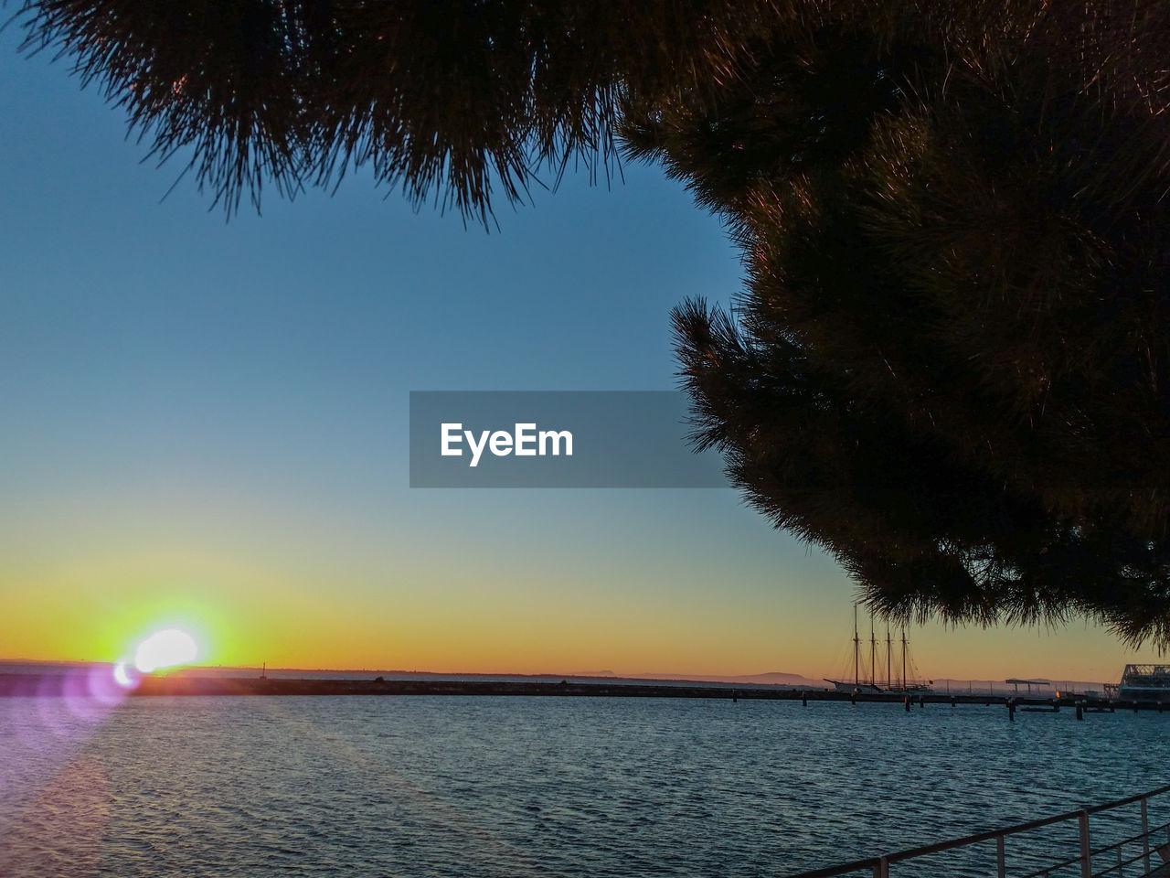 sky, water, tree, scenics - nature, sunset, tranquility, beauty in nature, plant, tranquil scene, nature, no people, clear sky, outdoors, non-urban scene, sea, orange color, blue, land, winter