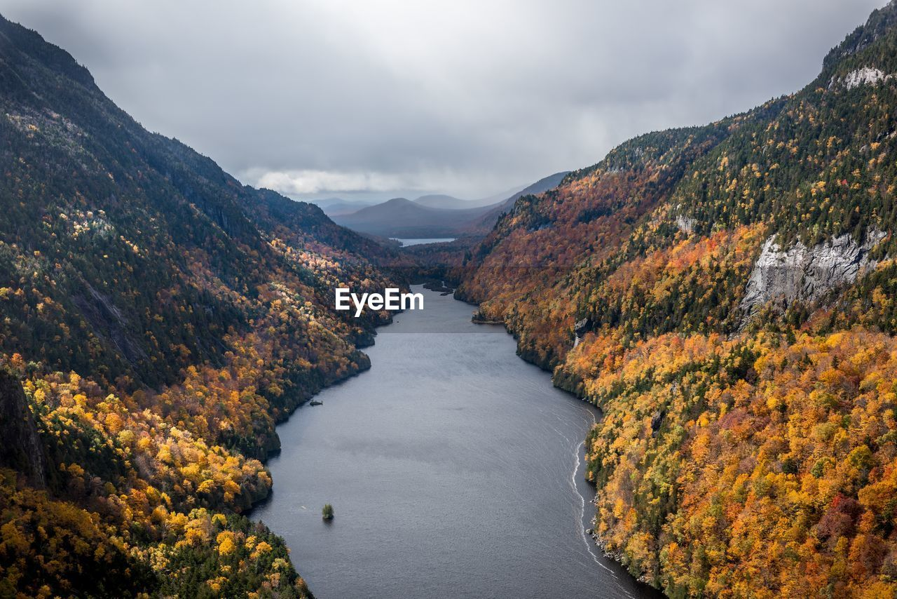 SCENIC VIEW OF RIVER AMIDST MOUNTAINS DURING AUTUMN