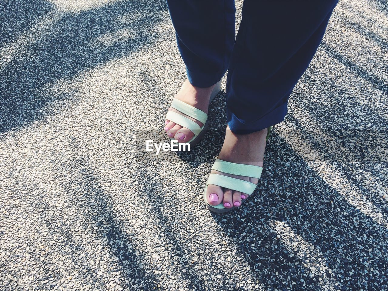 Low Section Of Woman Wearing Sandals Standing On Road