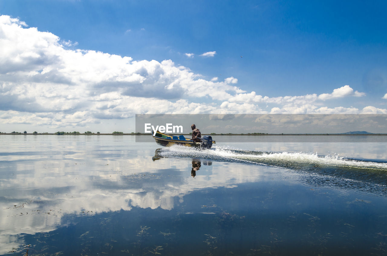 Man in motorboat on lake against cloudy sky