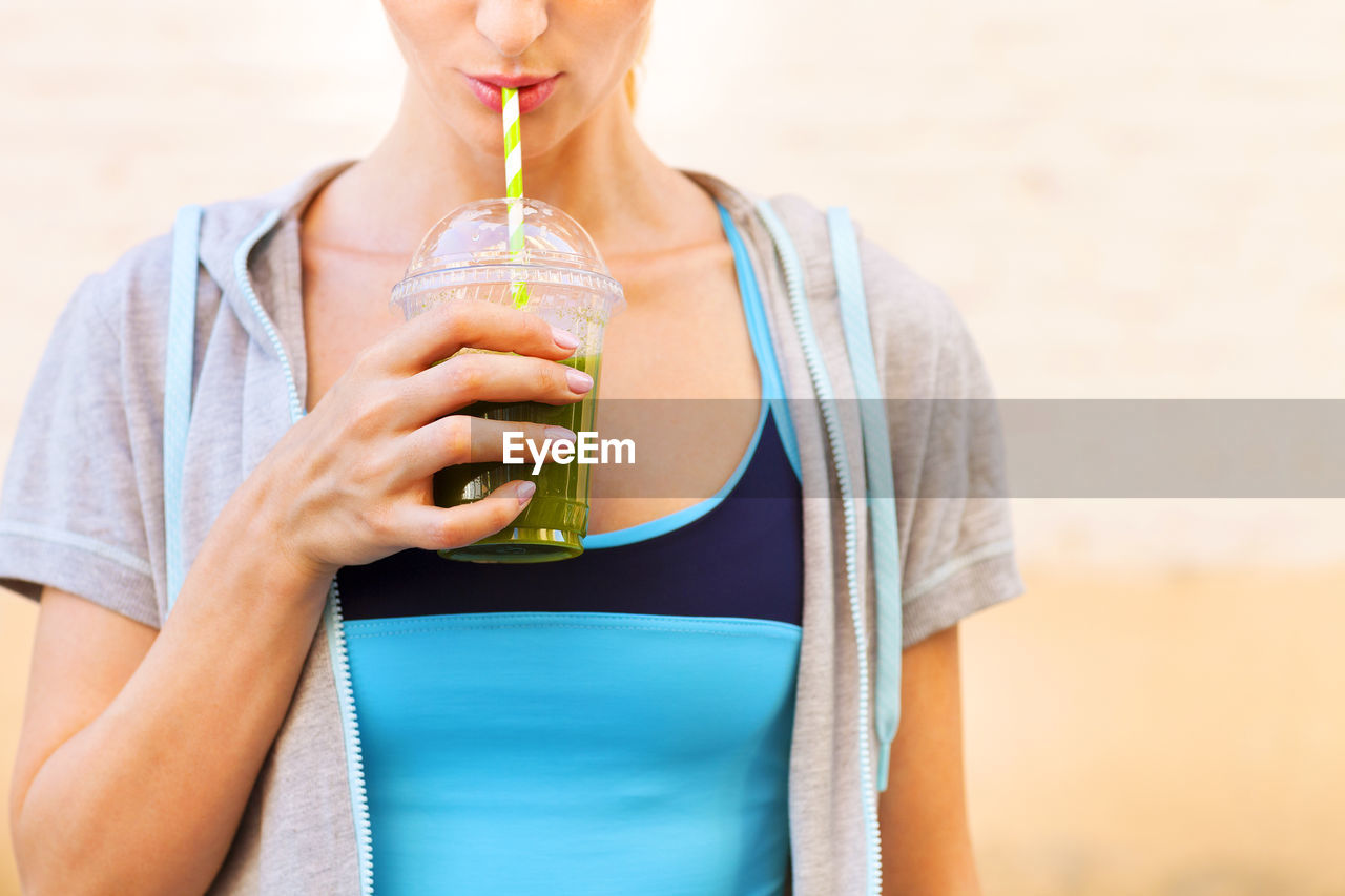 MIDSECTION OF WOMAN HOLDING ICE CREAM CONE