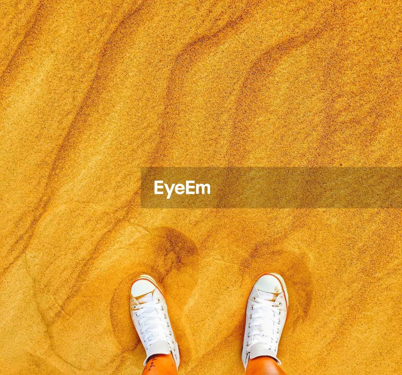 Low Section Of Person Standing On Sand In Desert