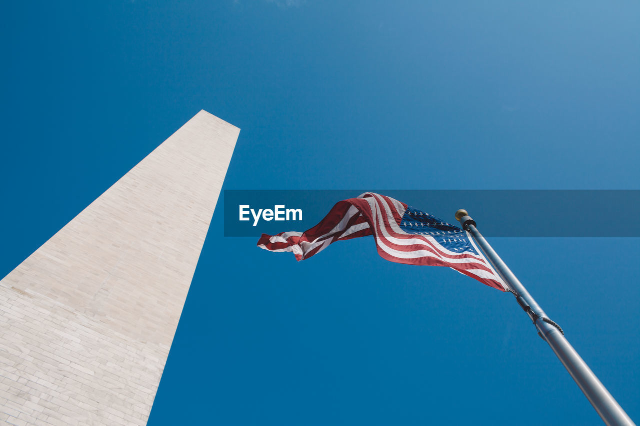Low Angle View Of American Flag By Washington Monument Against Clear Sky