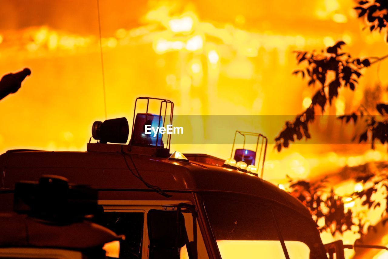sunset, mode of transportation, car, nature, transportation, motor vehicle, no people, land vehicle, focus on foreground, orange color, sky, illuminated, technology, photography themes, outdoors, yellow, communication, silhouette, table, tree, glass, nightlife