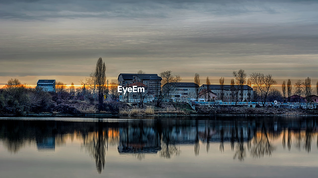 built structure, architecture, building exterior, reflection, sky, water, sunset, no people, tree, outdoors, city, nature, day