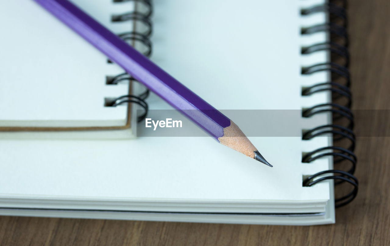 still life, no people, close-up, table, writing instrument, education, spiral, indoors, pencil, office supply, pen, high angle view, spiral notebook, paper, selective focus, publication, book, wood - material, page, sharp, note pad