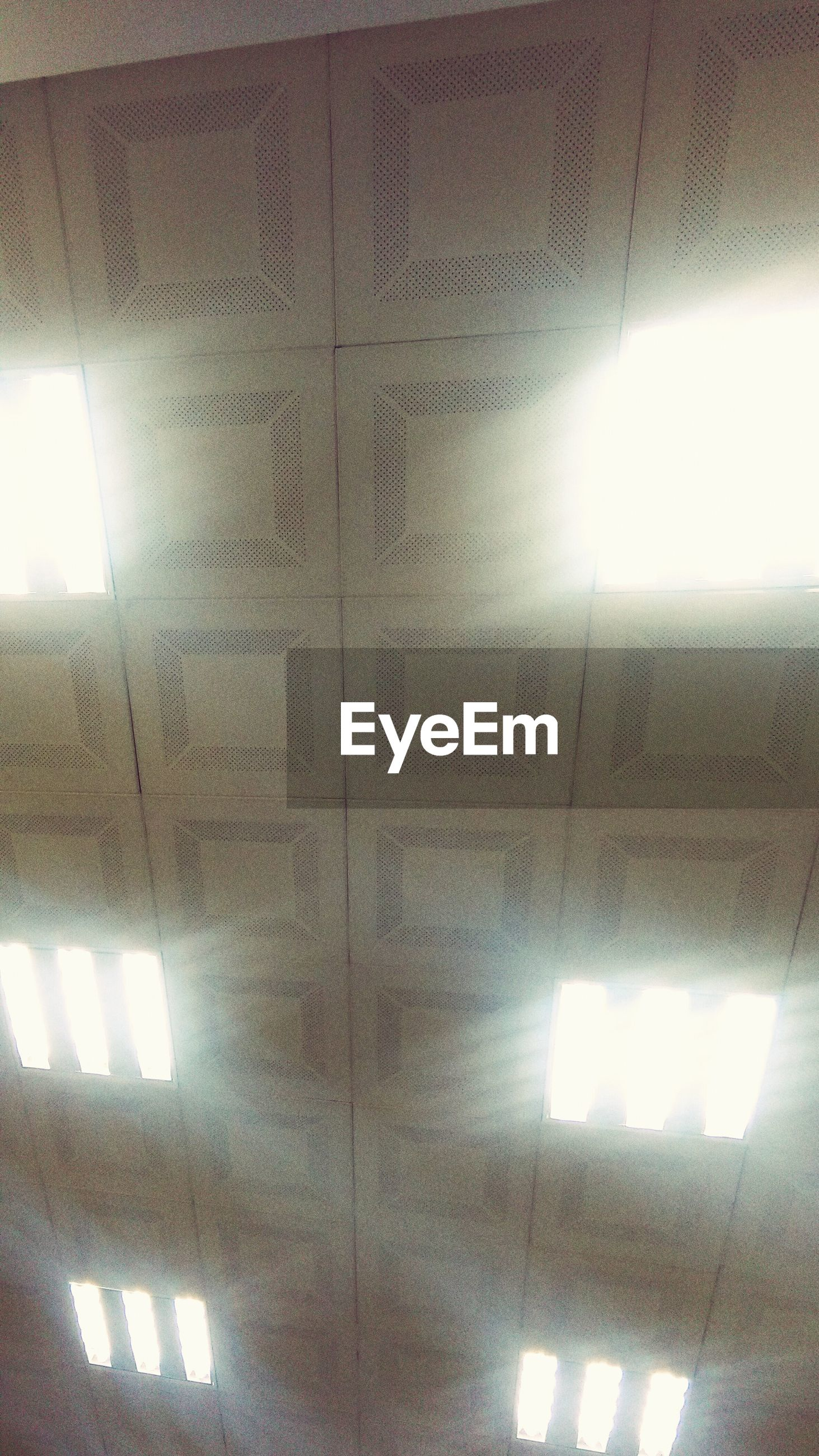 indoors, architecture, illuminated, built structure, ceiling, low angle view, lighting equipment, wall - building feature, pattern, full frame, window, backgrounds, building, light - natural phenomenon, wall, geometric shape, no people, home interior, sunlight, directly below