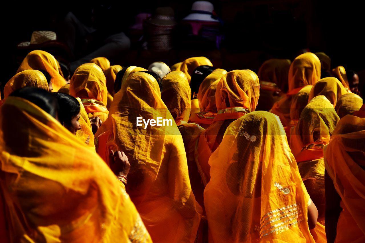 Rear View Of Women Wearing Yellow Sari