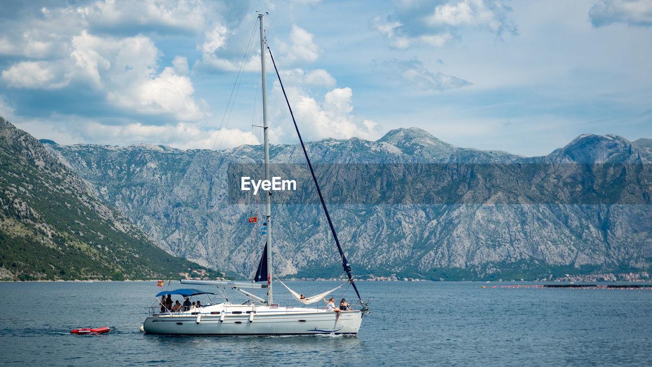 Sailboat Sailing On Sea Against Mountains