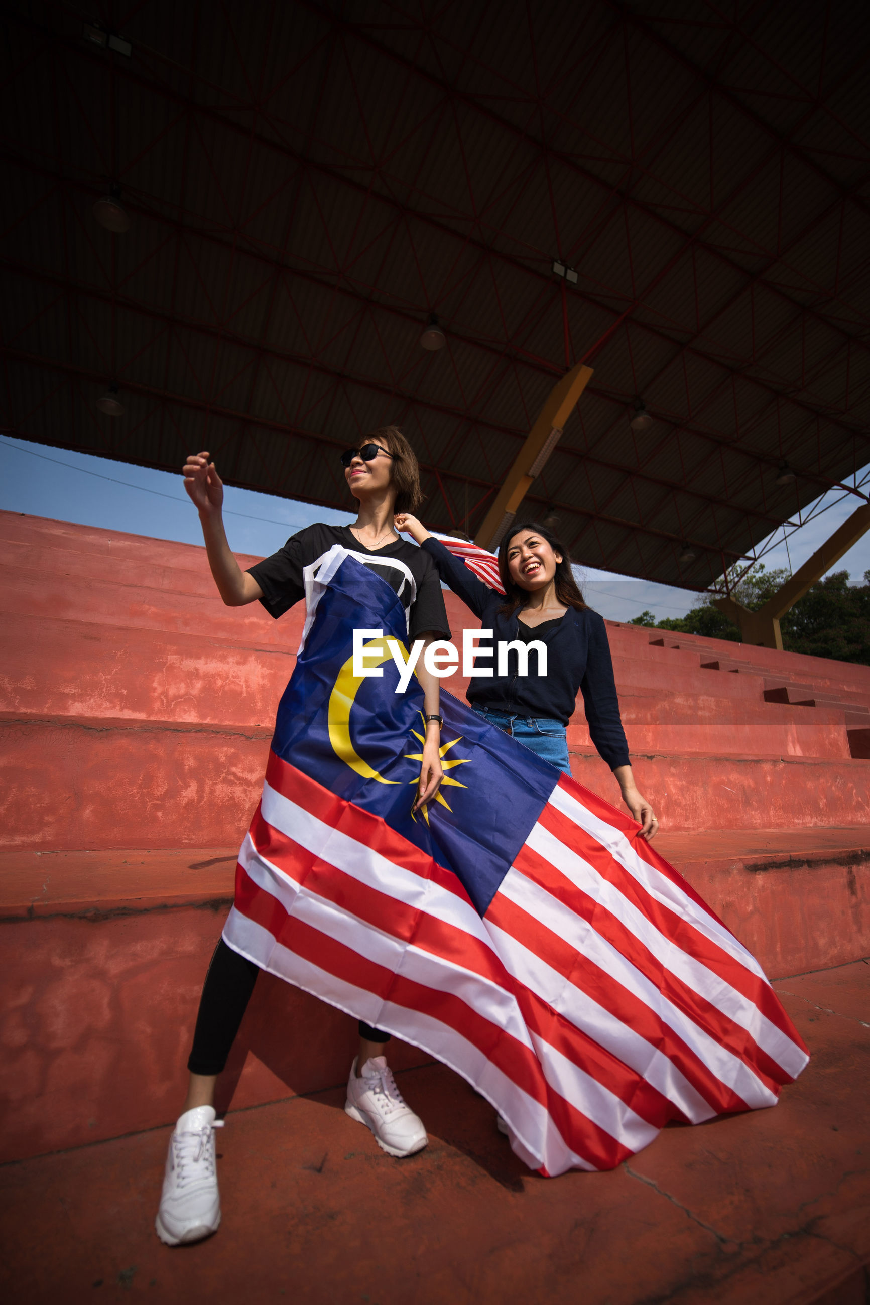 Friends with malaysian flag standing in stadium