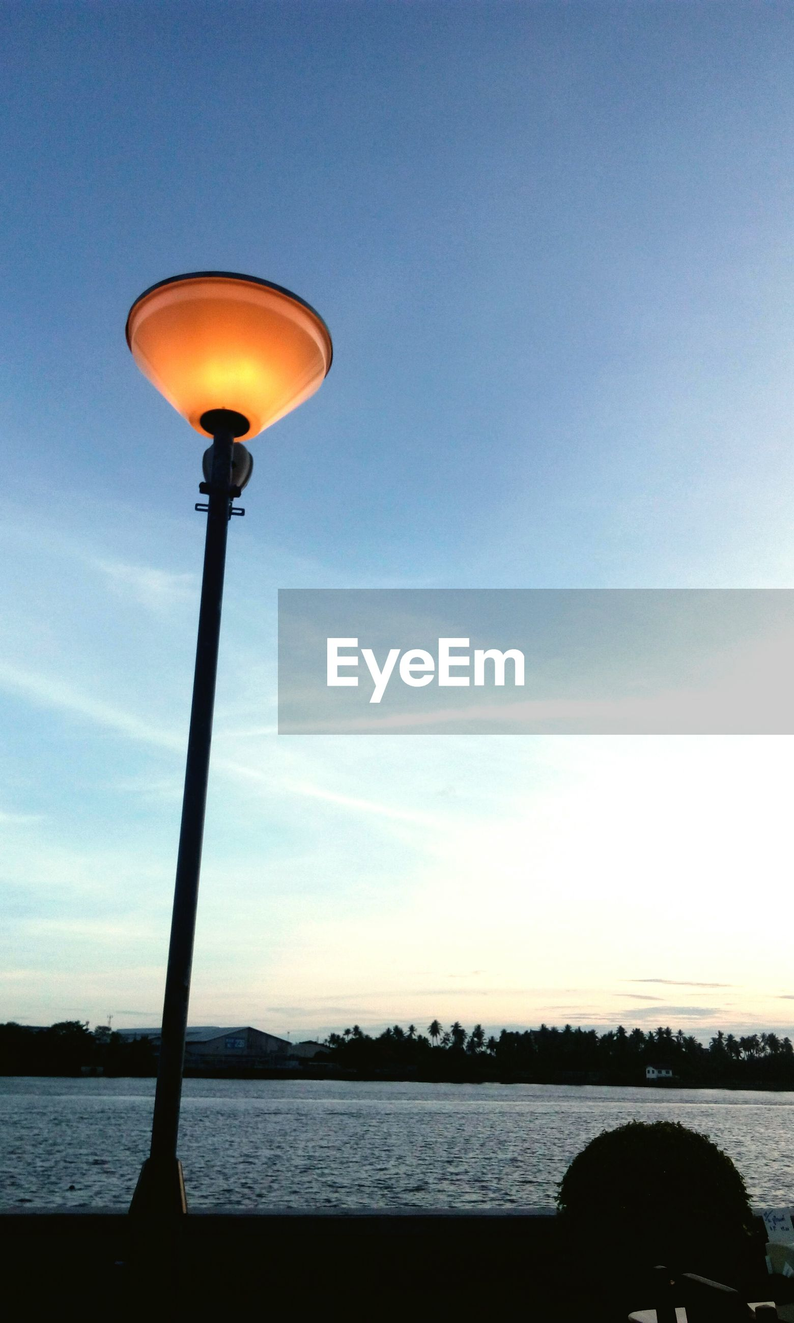 Low angle view of illuminated street light by lake against sky