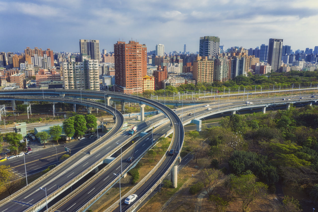 architecture, transportation, city, building exterior, built structure, road, sky, cityscape, cloud - sky, motor vehicle, bridge, highway, connection, mode of transportation, nature, building, car, office building exterior, land vehicle, high angle view, bridge - man made structure, multiple lane highway, no people, modern, skyscraper, outdoors
