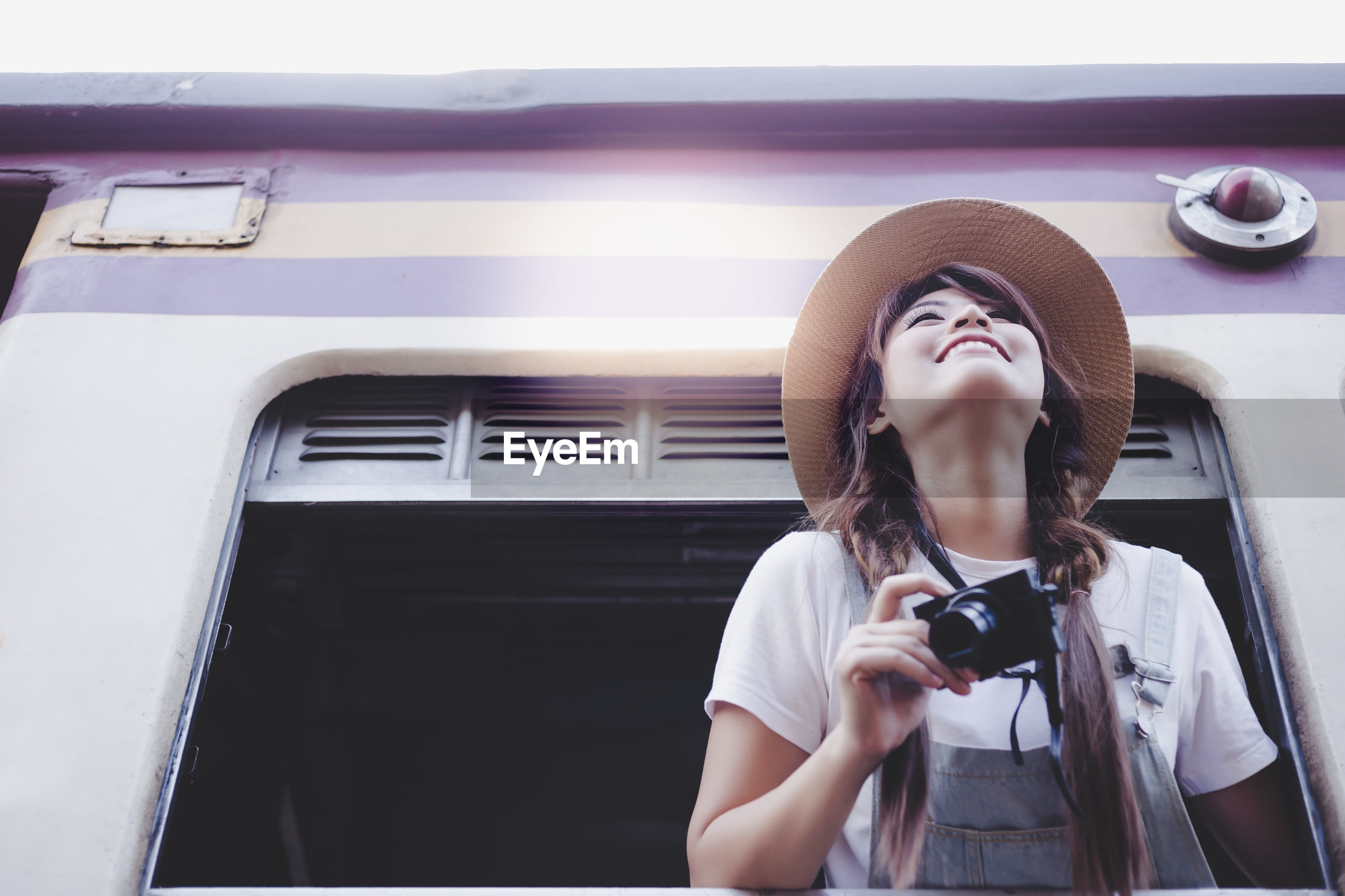 Smiling passenger holding camera while leaning on window of train
