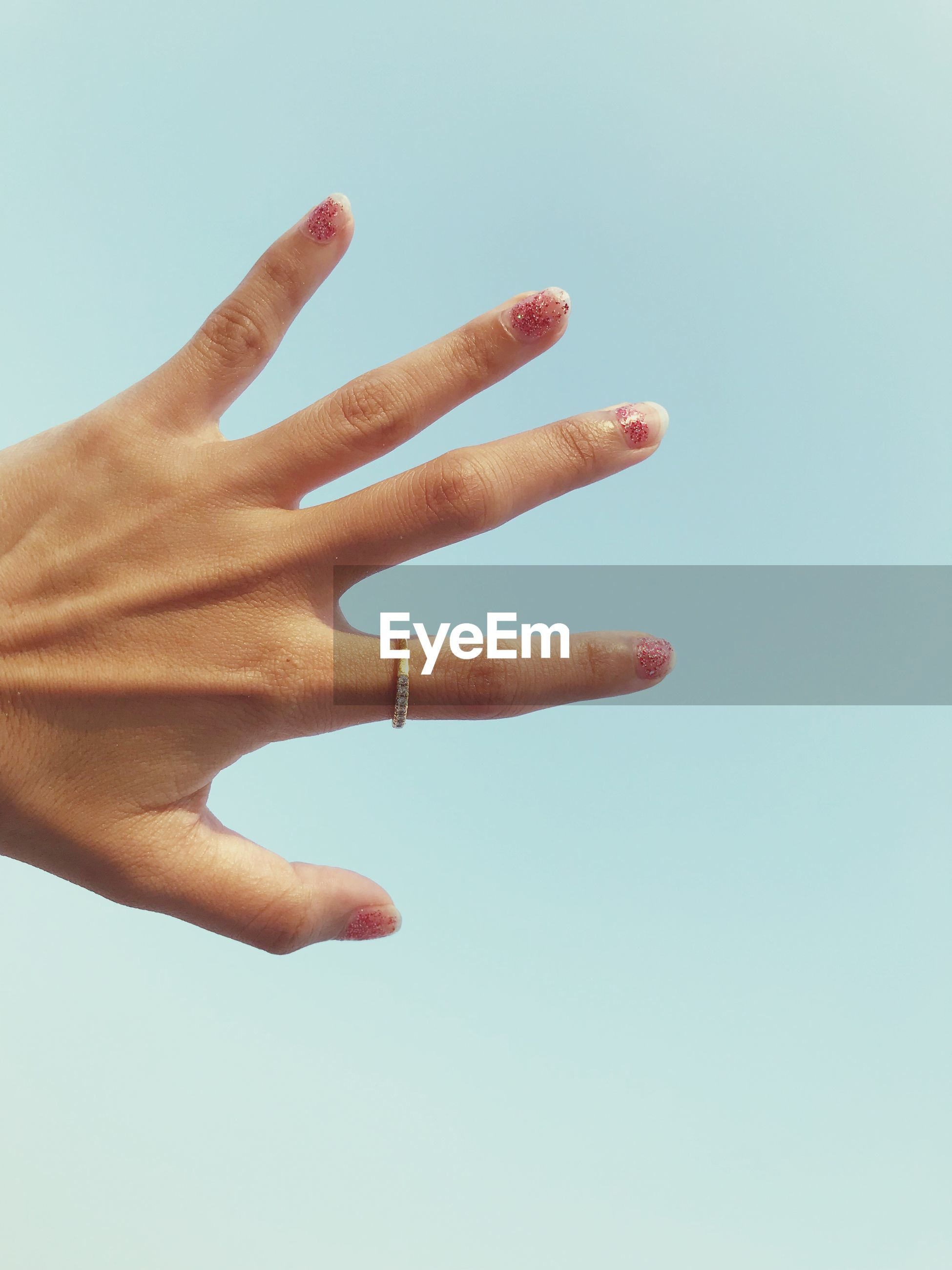 Cropped hand of woman against blue sky