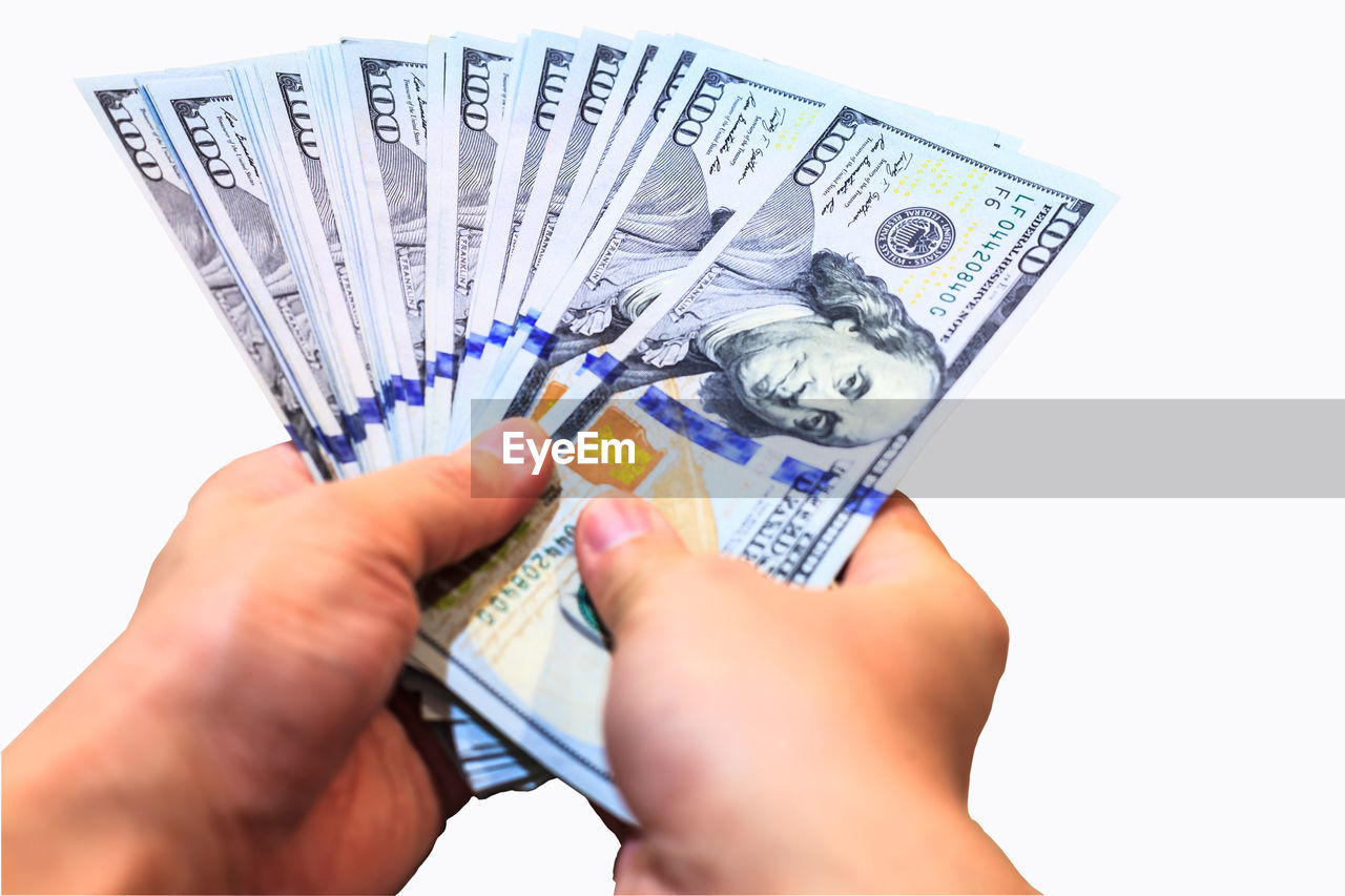 Close-up of hand holding us paper currency over white background
