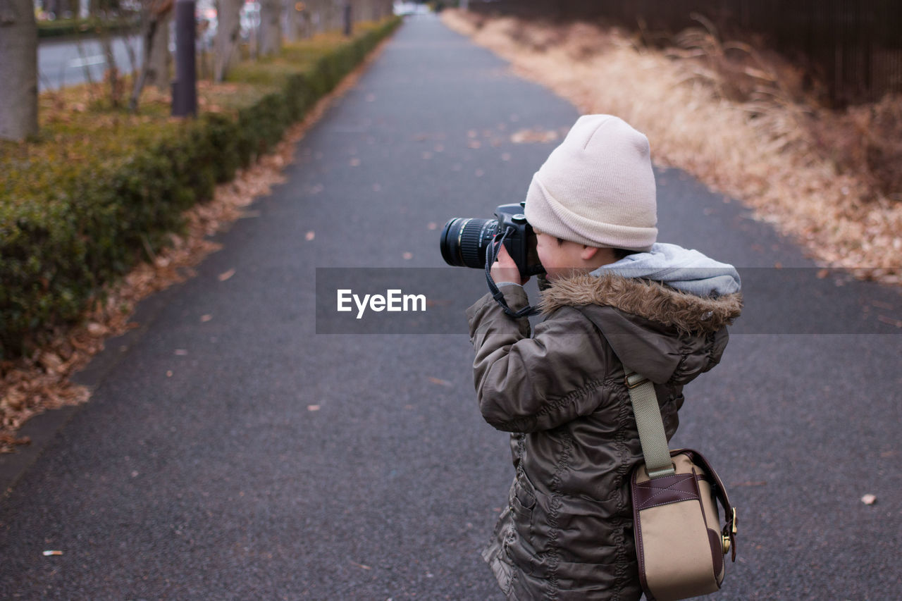 Side view of boy photographing with camera on street