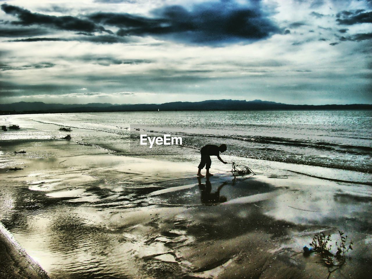 Silhouette boy playing at beach against cloudy sky