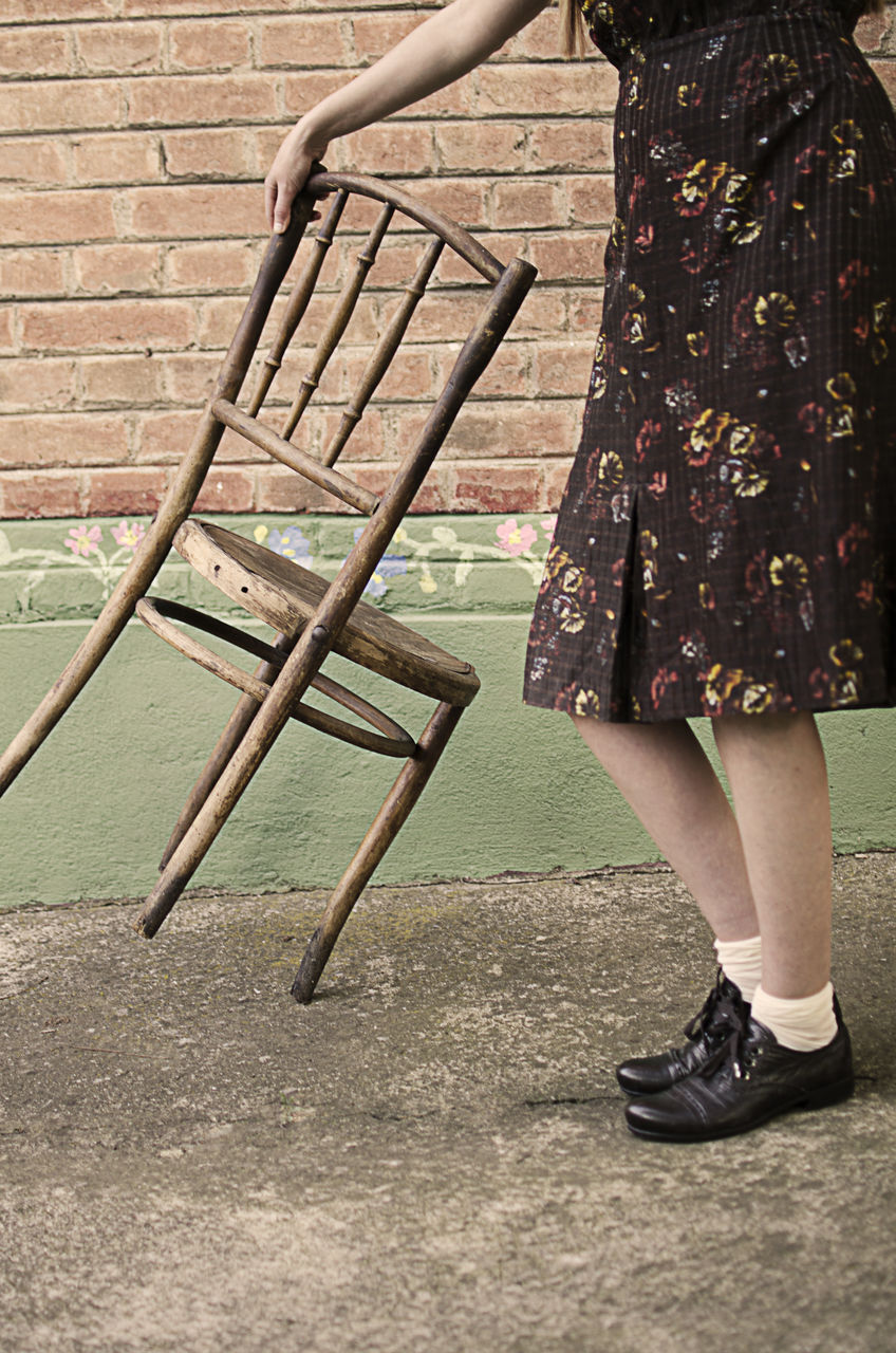 Low section of woman with chair standing by brick wall