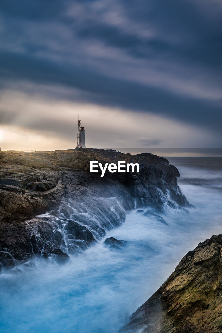 sky, sea, water, cloud - sky, tower, built structure, building exterior, beauty in nature, scenics - nature, guidance, architecture, motion, nature, land, lighthouse, rock, rock - object, solid, building, no people, horizon over water, outdoors, power in nature
