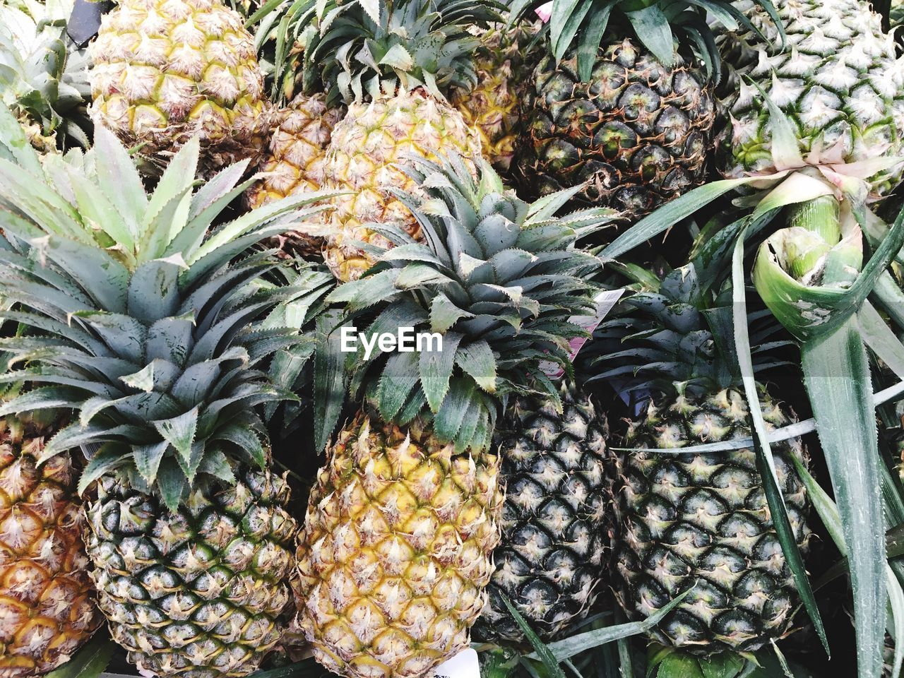pineapple, food and drink, market, fruit, healthy eating, food, freshness, for sale, no people, variation, retail, outdoors, day, abundance, choice, nature, beauty in nature, close-up