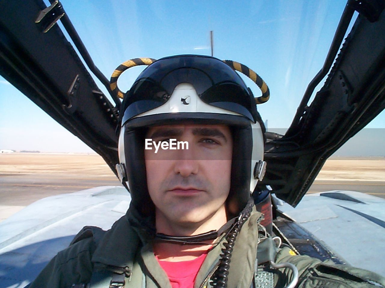 real people, transportation, one person, air vehicle, headshot, front view, day, portrait, leisure activity, young adult, looking at camera, outdoors, helmet, headwear, lifestyles, sky, airplane, warm clothing, close-up, people