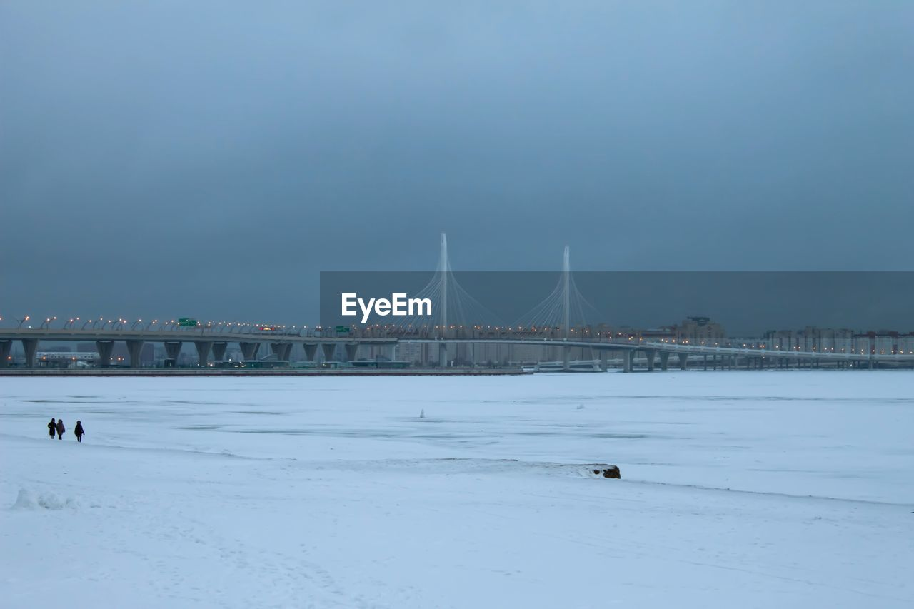 cold temperature, winter, built structure, snow, sky, architecture, connection, nature, bridge, bridge - man made structure, day, building exterior, white color, travel destinations, travel, water, beauty in nature, covering, transportation, outdoors, snowcapped mountain
