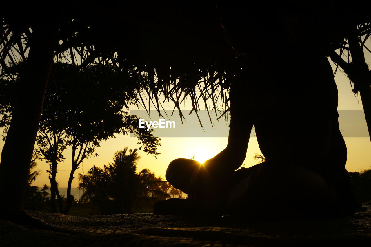 Silhouette man sitting outdoors during sunset