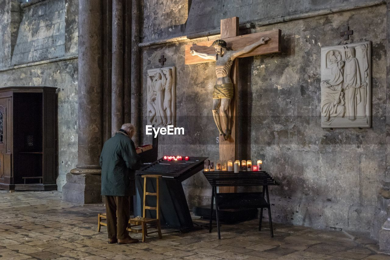 religion, spirituality, seat, architecture, belief, place of worship, building, cross, candle, built structure, crucifix, chair, sculpture, human representation, indoors, art and craft