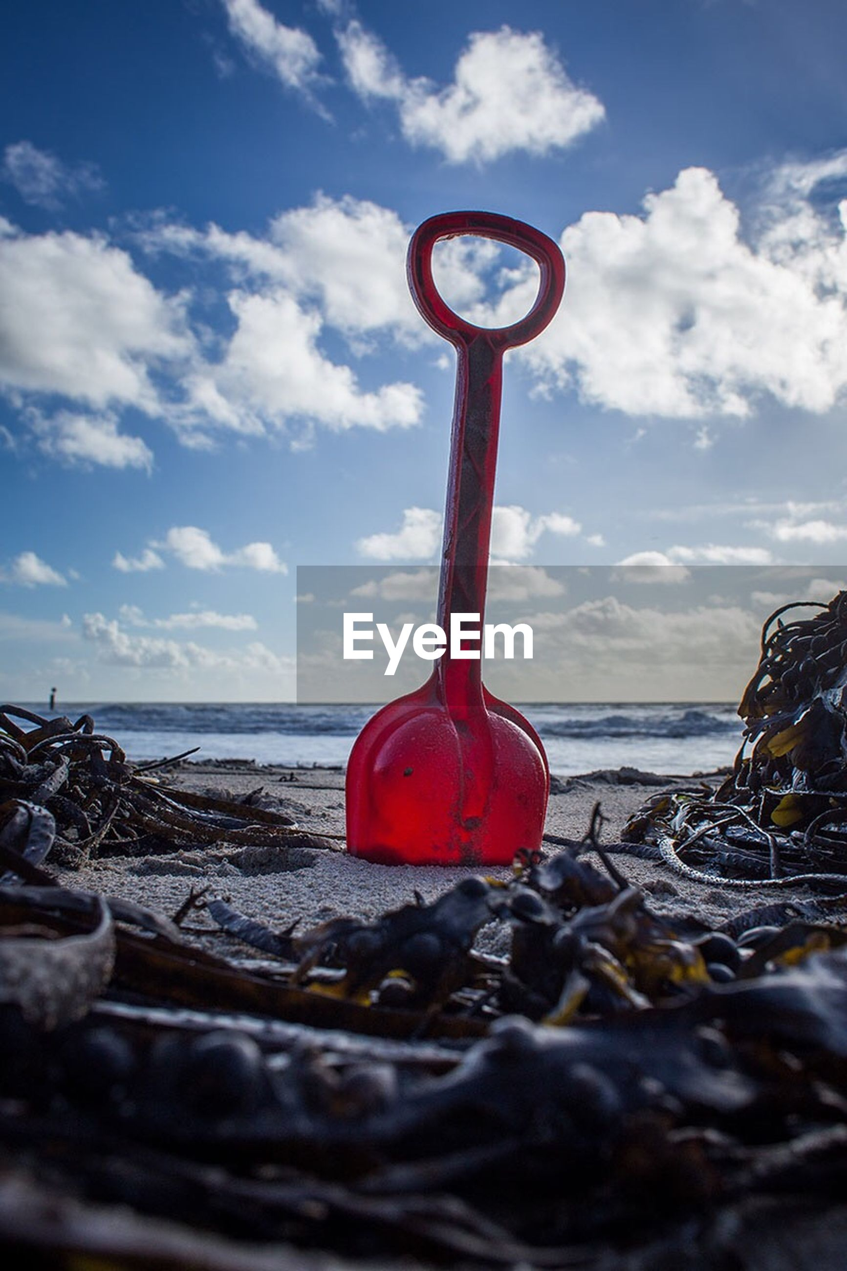 sea, water, sky, red, horizon over water, beach, shore, safety, cloud - sky, tranquility, protection, guidance, cloud, tranquil scene, day, outdoors, circle, stone - object, metal, sand