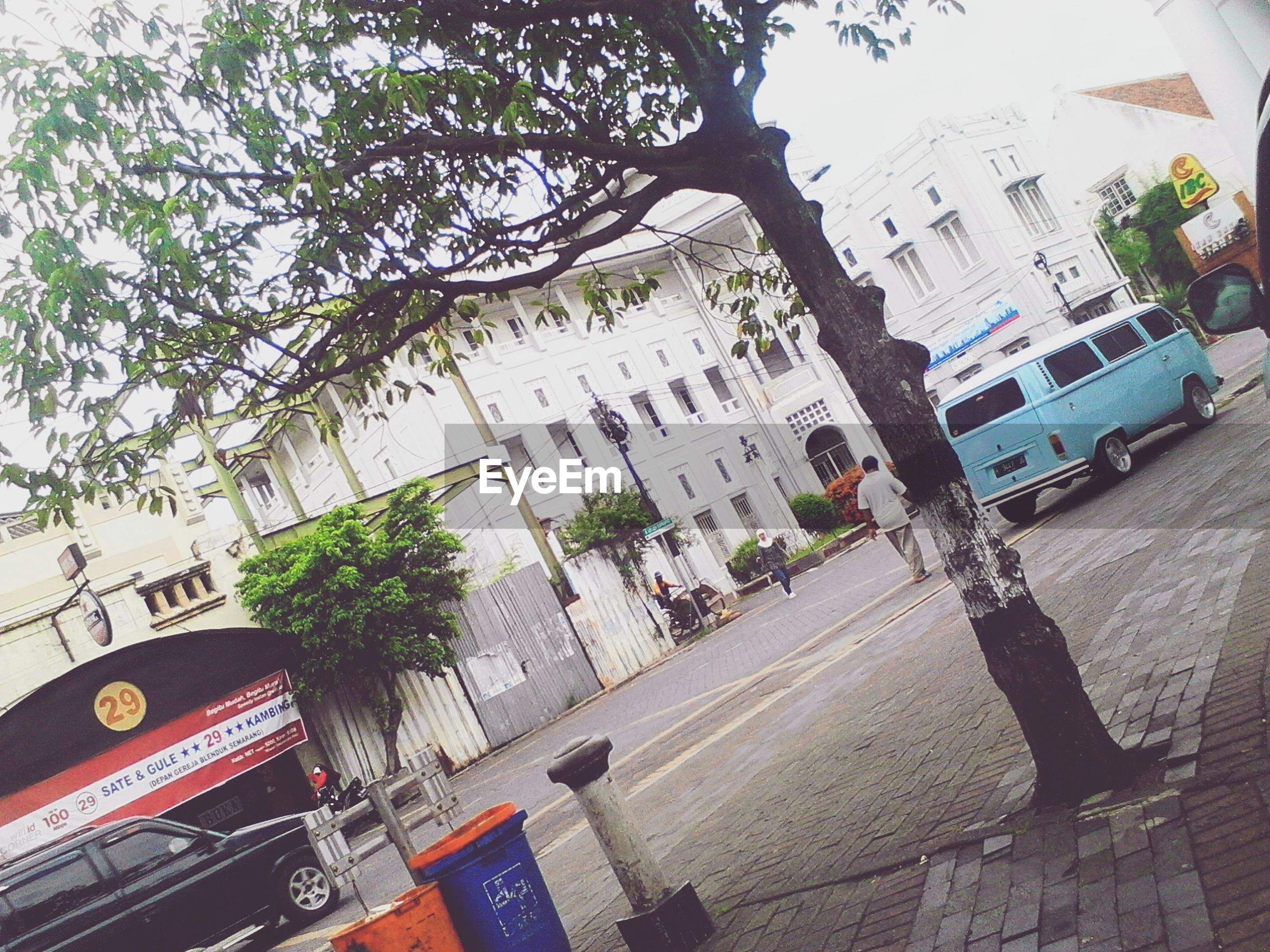 building exterior, architecture, built structure, city, street, tree, car, road, text, transportation, building, land vehicle, high angle view, city life, city street, incidental people, communication, day, residential building, western script