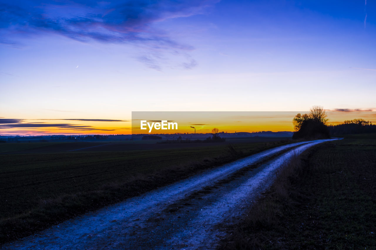 sunset, landscape, sky, nature, field, tranquil scene, no people, scenics, beauty in nature, tranquility, agriculture, the way forward, outdoors, rural scene, road, blue, day
