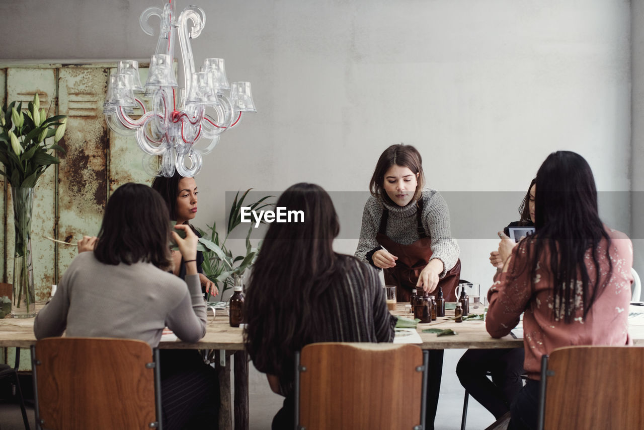 real people, group of people, sitting, women, table, young women, indoors, casual clothing, seat, chair, young adult, togetherness, lifestyles, people, three quarter length, long hair, adult, friendship, leisure activity, business, hairstyle