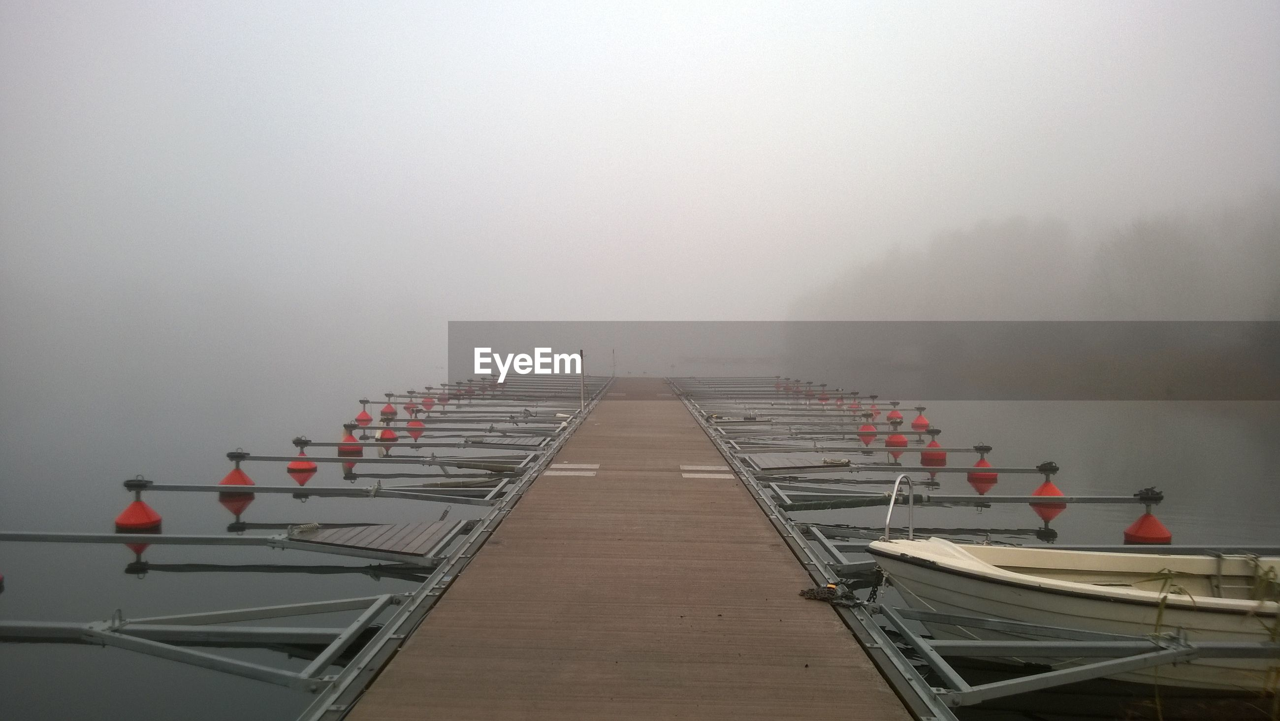 Pier over river in foggy weather