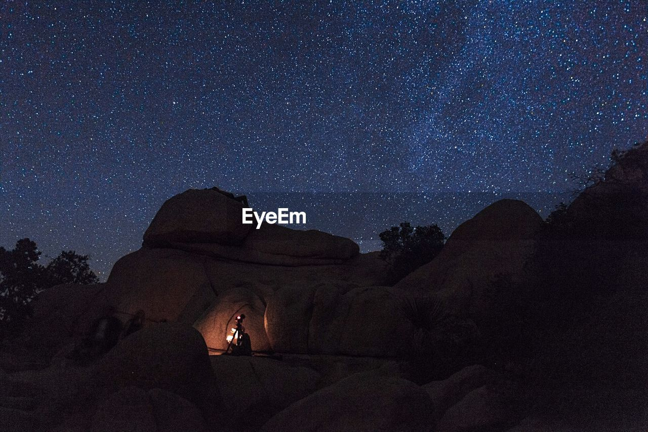Silhouette Of Photographer On Rocks Against Sky At Night