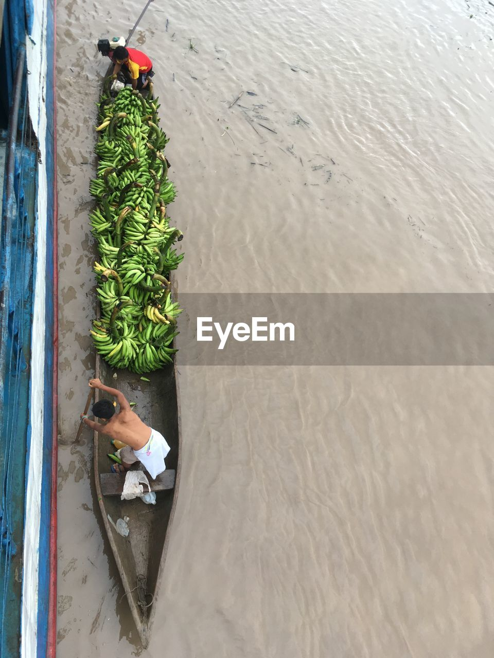 Directly above shot of man rowing canoe full on bananas on river